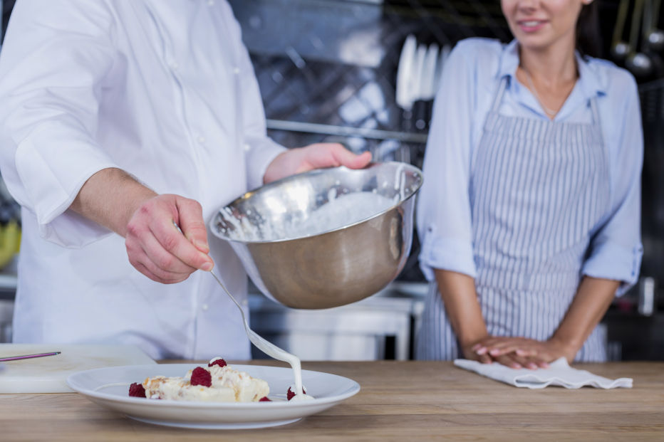 Sweet cream. Confident experienced chef adding some cream to a dessert while cooking it
